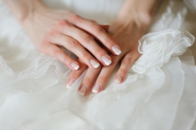 Mãos da noiva com uma manicure no vestido dela