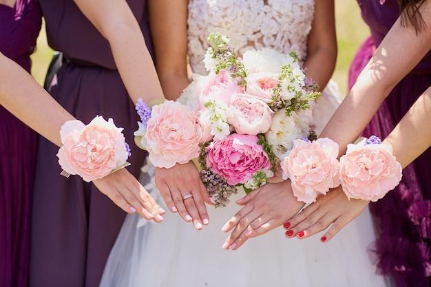 Mãos da noiva e da namorada com flores decorativas