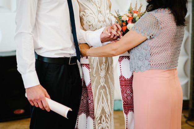 Mãos da noiva e do noivo amarradas toalhas de casamento