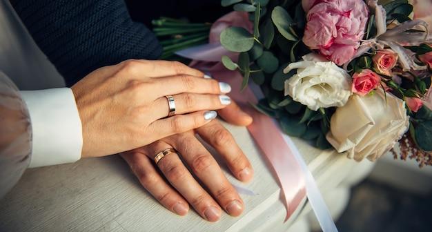 Mãos da noiva e do noivo, buquê de casamento, vista superior.