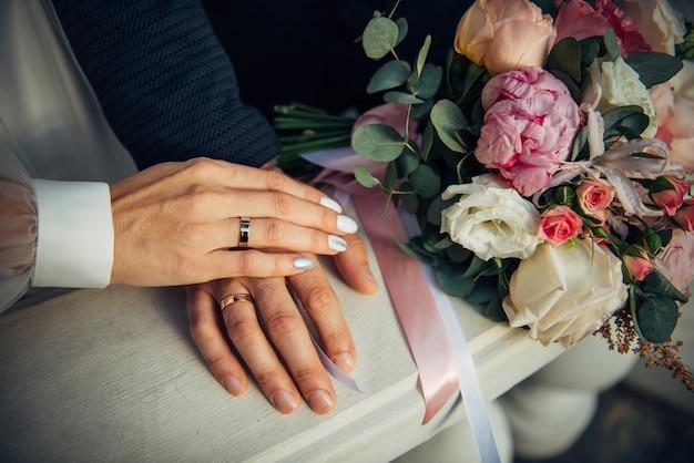 Mãos da noiva e do noivo, buquê de casamento