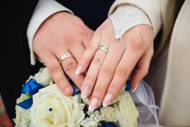 Mãos da noiva e do noivo com alianças de casamento de um lindo buquê