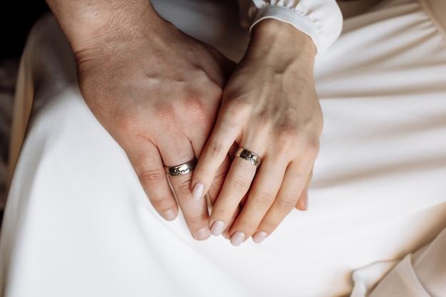 Mãos da noiva e do noivo com alianças de ouro. casamento .