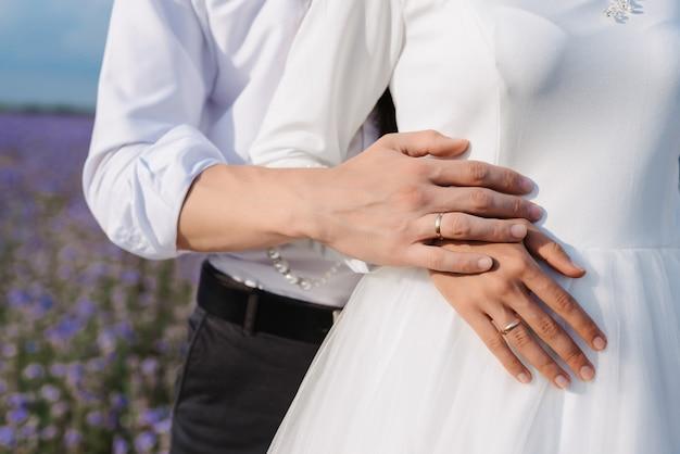 Mãos da noiva e do noivo com alianças de ouro no fundo de um vestido branco