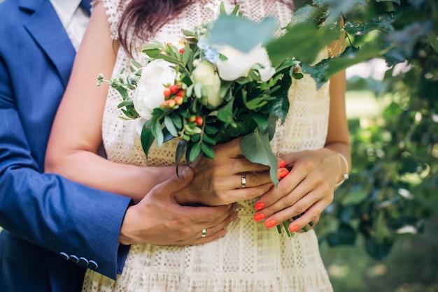 Mãos da noiva e do noivo com anéis de casamento, buquê de flores frescas, vestido vintage de renda