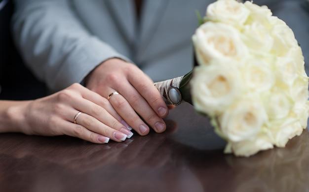 Mãos da noiva e do noivo com anéis de casamento e buquê de rosas