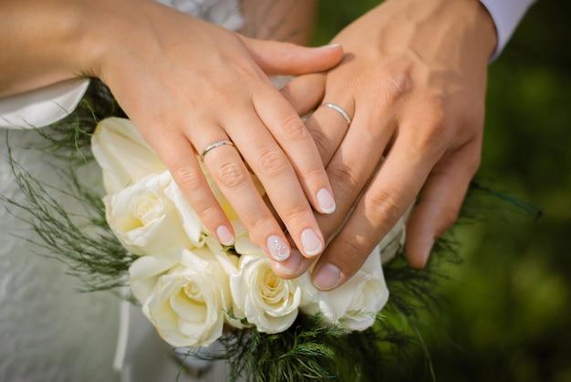Mãos da noiva e do noivo com anéis de casamento em um buquê de rosas brancas