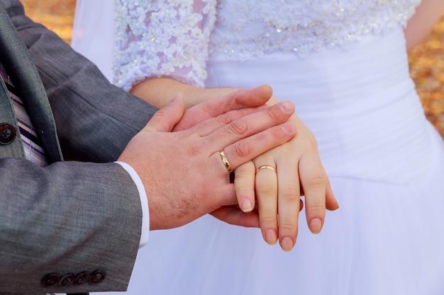 Mãos da noiva e do noivo com anéis de casamento