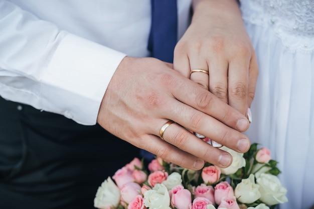 Mãos da noiva e do noivo com anéis de ouro do buquê de casamento