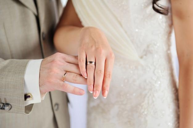 Mãos da noiva e do noivo com anéis de ouro no casamento. Foto Premium