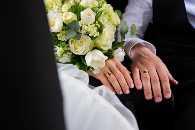 Mãos da noiva e do noivo com anéis e buquê de flores