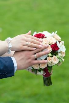 Mãos da noiva e do noivo com anéis em um buquê de casamento