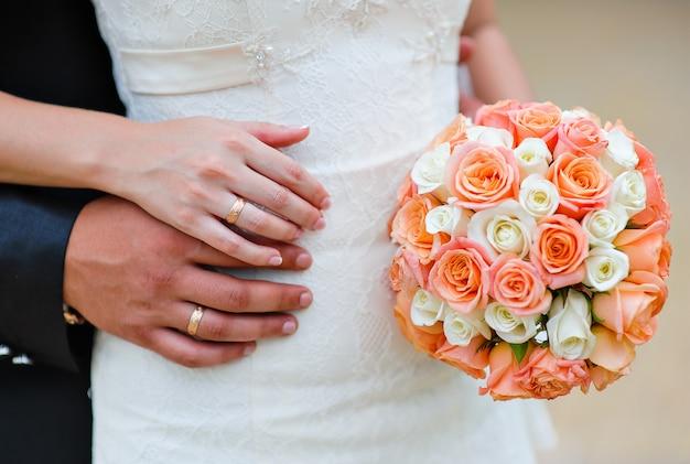Mãos da noiva e do noivo com anéis em um fundo de um buquê de casamento
