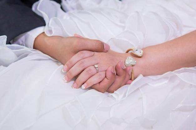 Mãos da noiva e do noivo com anéis interpretação do amor