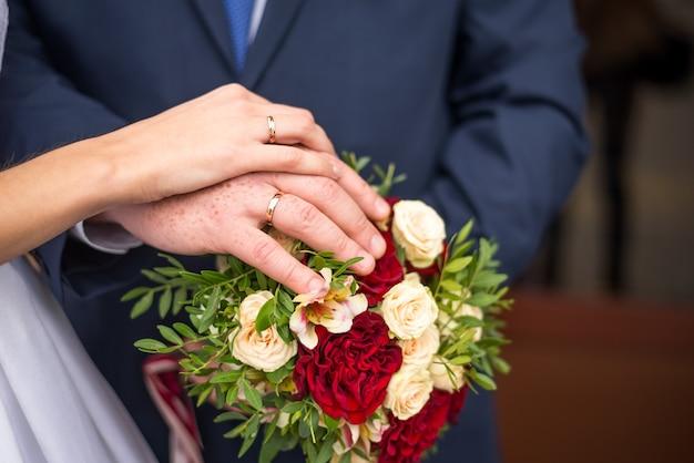 Mãos da noiva e do noivo com anéis no buquê de casamento. conceito de casamento ..