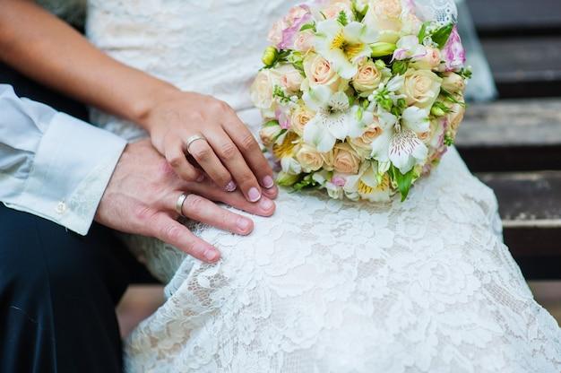 Mãos da noiva e do noivo com anéis no buquê de casamento.