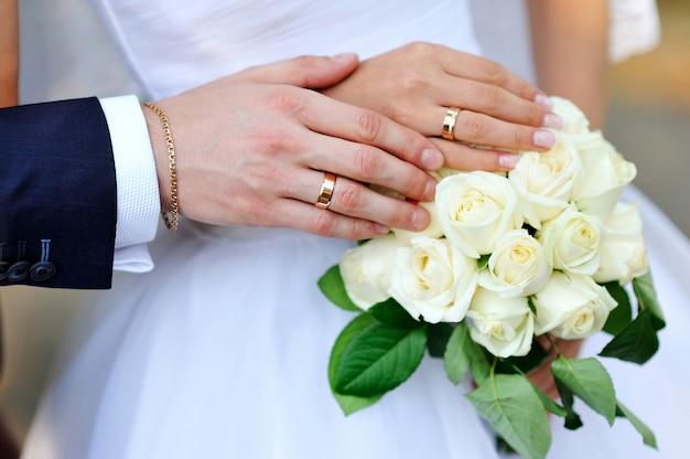 Mãos da noiva e do noivo com anéis no buquê de casamento