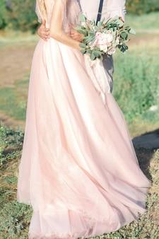 Mãos da noiva e do noivo com buquê de flores. fotografia de belas artes.