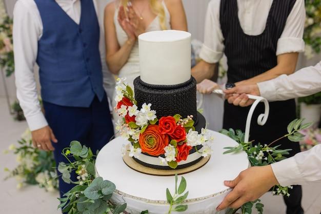 Mãos da noiva e do noivo, cortam uma fatia de um bolo de casamento.
