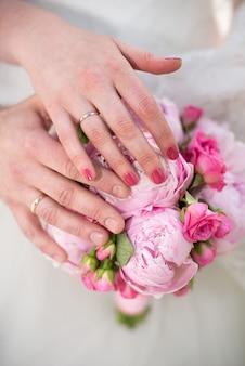 Mãos da noiva e do noivo em um buquê.