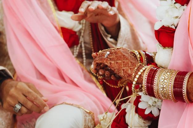 Mãos da noiva e do noivo indiano na cerimônia de casamento tradicional