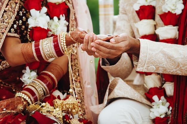 Mãos da noiva e do noivo indianos entrelaçados, fazendo um ritual de casamento autêntico