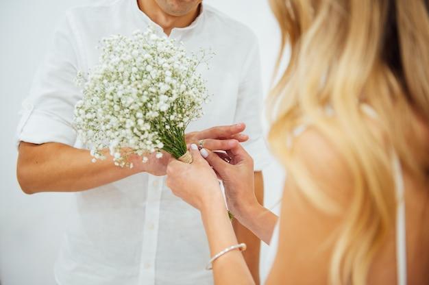 Mãos da noiva e do noivo. noiva e noivo em uma cerimônia de casamento de mãos dadas. alianças de casamento nas mãos dos recém-casados. recém-casados colocam anéis um no outro