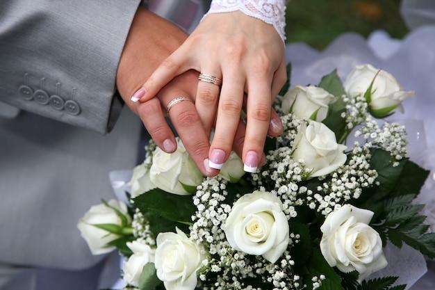 Mãos da noiva e do noivo perto do buquê de casamento