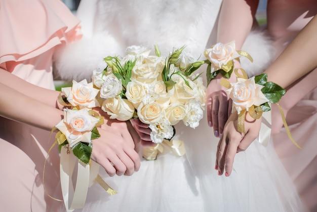 Mãos da noiva e suas damas de honra com um buquê