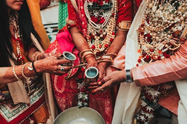 Mãos da noiva indiana cobertas com mehndi segurando pulseiras