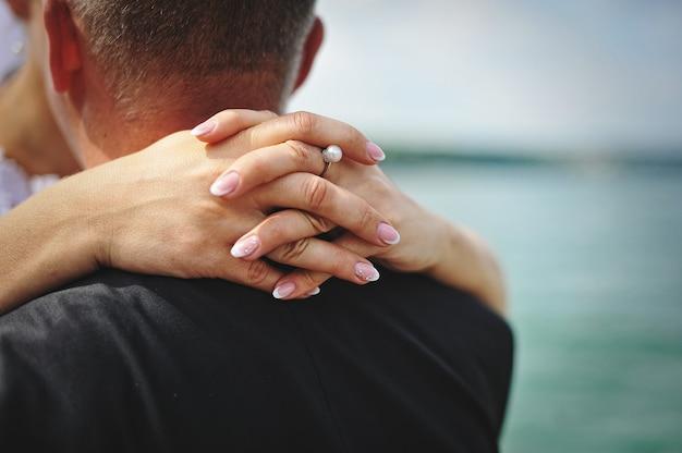 Mãos da noiva que abraçaram para pescoço seu noivo
