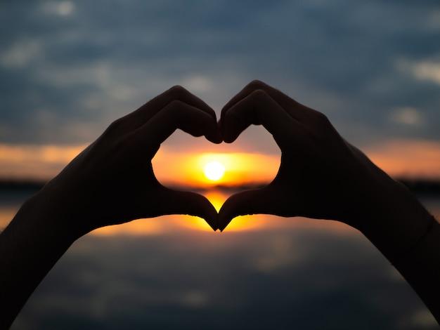 Mãos da silhueta a ser forma do coração no fundo do por do sol.