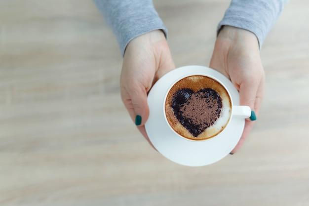 Mãos da vista superior que guardam a xícara de café branca. impressão de coração no café