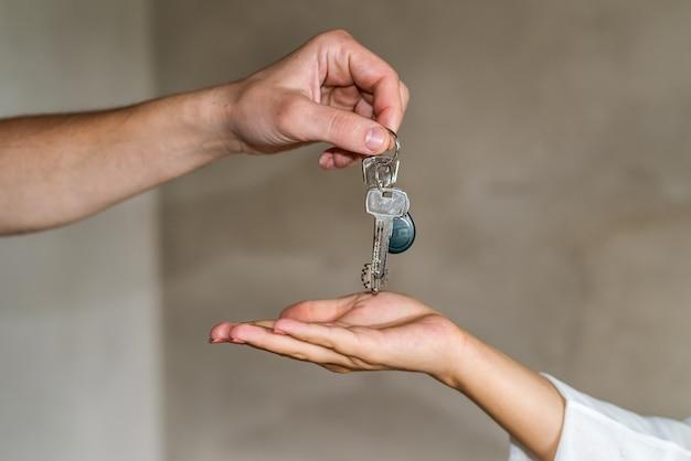 Mãos dando e recebendo chaves do apartamento