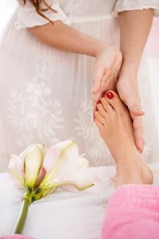 Mãos dando massagem nos pés, trabalhando no salão brilhante e agradável