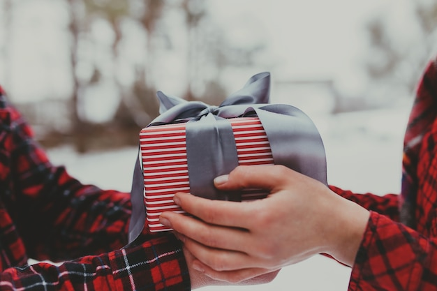 Mãos dando uma caixa de presente com fita.