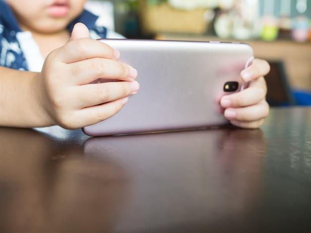 Mãos das crianças com o telefone móvel