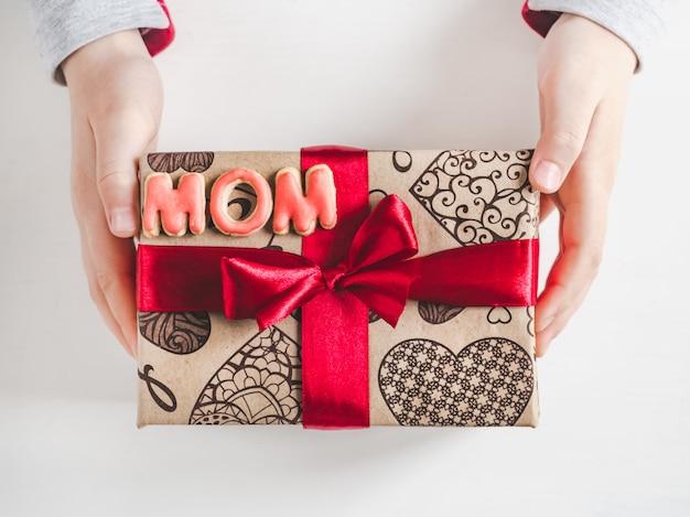 Mãos das crianças, linda caixa com um presente