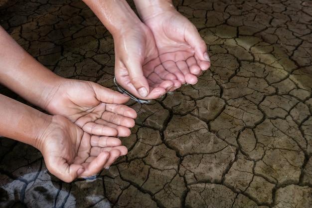 Mãos das crianças no solo árido.