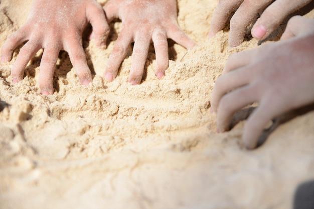Mãos das crianças que jogam a areia na praia. conceito de dia de verão. crianças felizes em férias à beira-mar.