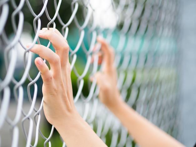 Mãos das mulheres que guardam a cerca no cenário exterior durante a luz do dia.