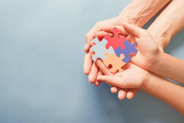 Mãos de adulto e criança segurando a forma de quebra-cabeça, conscientização do autismo, conceito de apoio à família do espectro do autismo, dia mundial da conscientização do autismo
