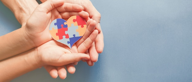 Mãos de adulto e criança segurando o quebra-cabeça em forma de coração, consciência do autismo, conceito de apoio à família do espectro do autismo, dia mundial da conscientização do autismo