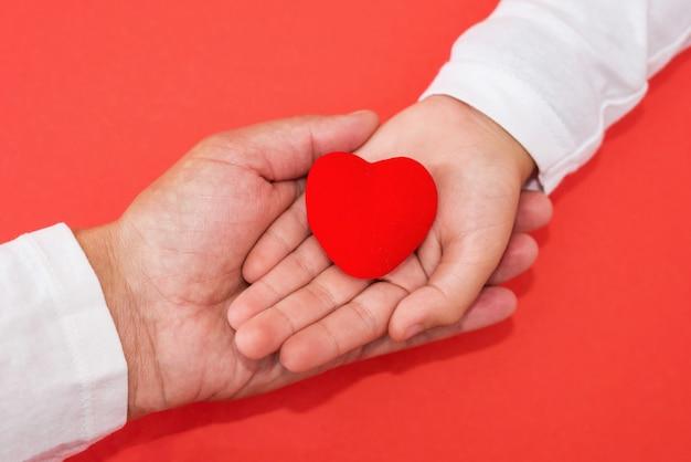 Mãos de adultos e crianças segurando um coração vermelho, amor de cuidados de saúde, dar, esperança e conceito de família, dia mundial do coração, dia mundial da saúde