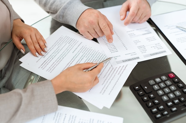 Mãos de agente e homem maduro apontando para documentos financeiros enquanto discutem informações de investimentos