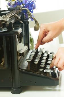 Mãos de alguém digitando em uma máquina de escrever preta vintage de perto