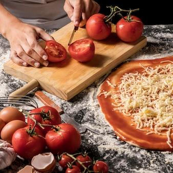 Mãos de alto ângulo cortando tomate