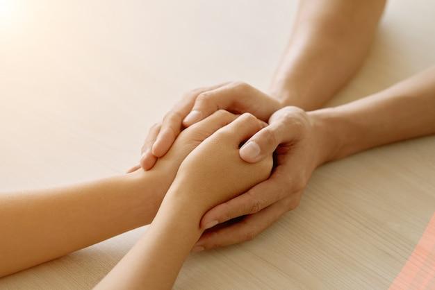 Mãos de amigo de apoio anônimo, segurando as mãos de mulher