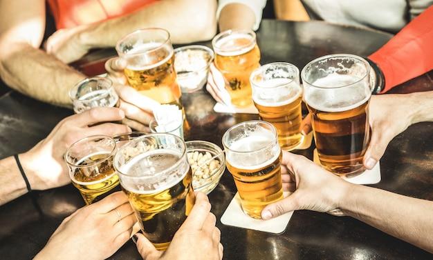 Mãos de amigos bebendo cerveja em restaurante-pub de cervejaria