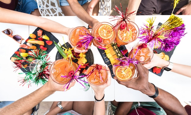 Mãos de amigos brindando coquetel de verão